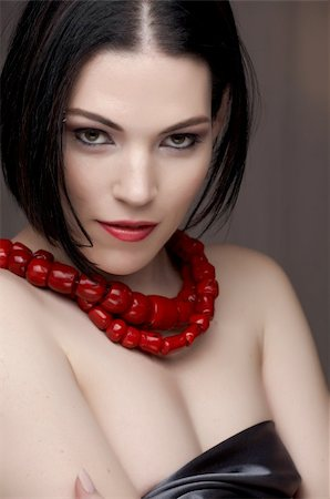 Sexy young caucasian adult woman with red lips, short black hair and a pierced eyebrow, covered in a dark satin sheet and wearing a red coral necklace Stock Photo - Budget Royalty-Free & Subscription, Code: 400-04236123