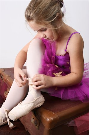 Young girl tying over sized pointe shoes dreaming of becoming a ballerina Stock Photo - Budget Royalty-Free & Subscription, Code: 400-04264593