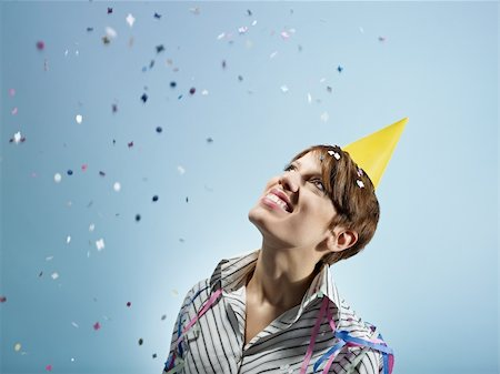 party celebration paper confetti - caucasian woman looking at confetti in the air. Horizontal shape, side view, head and shoulders, copy space Stock Photo - Budget Royalty-Free & Subscription, Code: 400-04267318