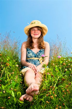 Young teenage girl sitting on summer meadow in straw hat Stock Photo - Budget Royalty-Free & Subscription, Code: 400-04268254