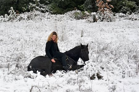 blond girl and her black stallion laid down in the snow Stock Photo - Budget Royalty-Free & Subscription, Code: 400-04269374