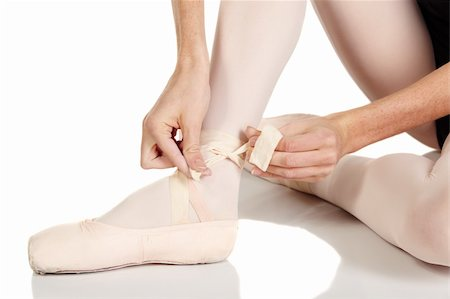 Young caucasian ballerina girl on white background and reflective white floor tying her ballet shoes. Not Isolated Stock Photo - Budget Royalty-Free & Subscription, Code: 400-04277902