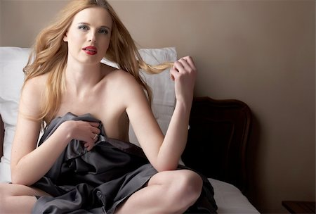 Sexy naked young caucasian adult woman with red lips and blonde hair sitting on a bed, covered with a dark silk sheet. Single light source Stock Photo - Budget Royalty-Free & Subscription, Code: 400-04277966