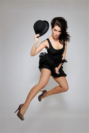sexy beautiful fashion woman in black dress jumping. gray background Stock Photo - Budget Royalty-Free & Subscription, Code: 400-04288035