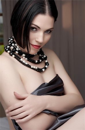 Sexy naked young caucasian adult woman with red lips, short black hair and a pierced eyebrow, covered in a dark satin sheet and wearing a black and white pearl string necklace Stock Photo - Budget Royalty-Free & Subscription, Code: 400-04298912