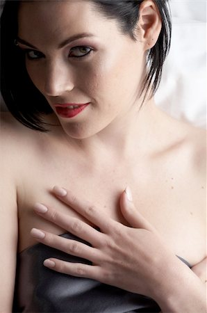 Sexy naked young caucasian adult woman with red lips, short black hair and a pierced eyebrow, covered in a dark satin sheet and sitting on a bed Stock Photo - Budget Royalty-Free & Subscription, Code: 400-04298913
