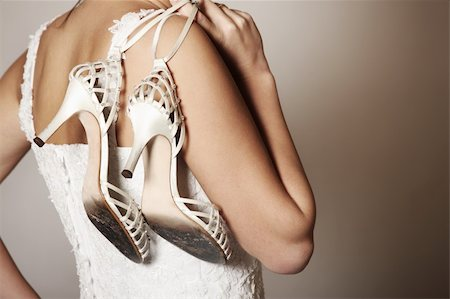 A portrait of the back of the bride carrying worn-out shoes Stock Photo - Budget Royalty-Free & Subscription, Code: 400-04292794