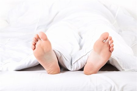 Men's feet under a white blanket Stock Photo - Budget Royalty-Free & Subscription, Code: 400-04307609