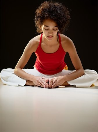 portrait of young adult latin american female sitting on white floor doing yoga exercise. Vertical shape, full length, front view, copy space Stock Photo - Budget Royalty-Free & Subscription, Code: 400-04316411