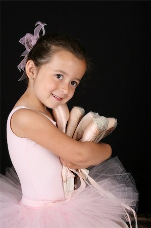 Cute brunette ballet girl holding lots of pointe shoes Stock Photo - Budget Royalty-Free & Subscription, Code: 400-04319401