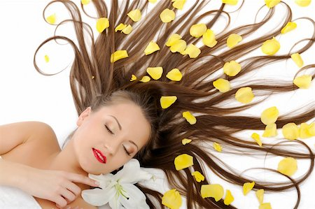 Beautiful spa woman with long healthy hair and bright make-up relaxing on the floor with yellow rose petals. isolated on white background Stock Photo - Budget Royalty-Free & Subscription, Code: 400-04326101