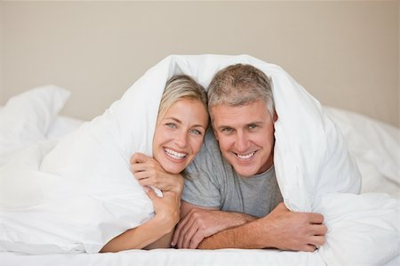 Couple lying down in their bed at home Stock Photo - Budget Royalty-Free & Subscription, Code: 400-04326377