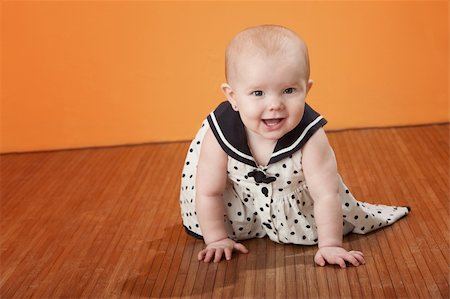photo of class with misbehaving kids - Cute baby in a polka dot dress crawls on a wooden floor Stock Photo - Budget Royalty-Free & Subscription, Code: 400-04328134