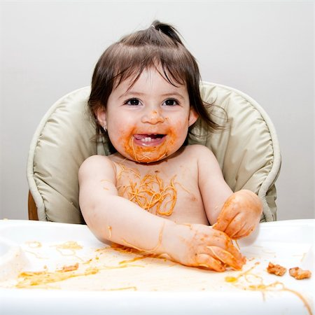 Happy baby having fun eating messy covered in Spaghetti Angel Hair Pasta red marinara tomato sauce. Stock Photo - Budget Royalty-Free & Subscription, Code: 400-04345317