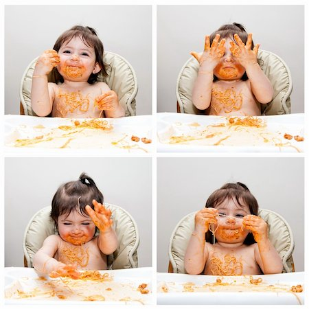 Happy baby having fun eating messy showing hands covered in Spaghetti Angel Hair Pasta red marinara tomato sauce. Stock Photo - Budget Royalty-Free & Subscription, Code: 400-04345318