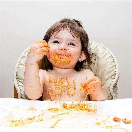 Happy smiling baby having fun eating messy covered in Spaghetti Angel Hair Pasta red marinara tomato sauce. Stock Photo - Budget Royalty-Free & Subscription, Code: 400-04345319
