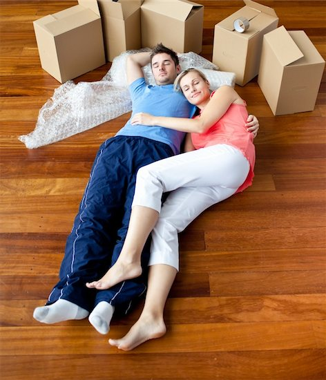 Couple lying on floor by close boxes in new home smiling Stock Photo - Royalty-Free, Artist: 4774344sean, Image code: 400-04341655