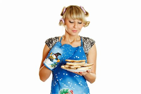 Pretty young woman in an apron and oven gloves holding a plate of gingerbread cookies. Isolated on a white background Stock Photo - Budget Royalty-Free & Subscription, Code: 400-04354613