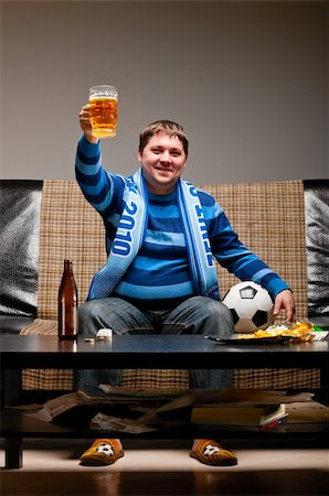 fat man balls - soccer fan is sitting on sofa with beer at home Stock Photo - Budget Royalty-Free & Subscription, Code: 400-04358886