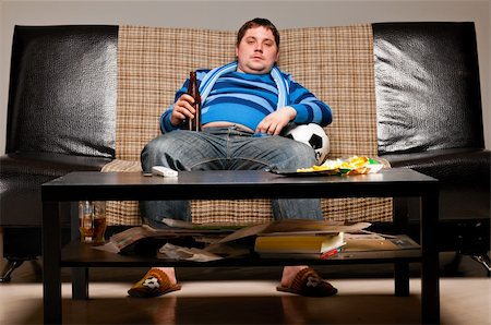 fat man balls - soccer fan is sitting on sofa with beer at home Stock Photo - Budget Royalty-Free & Subscription, Code: 400-04358887