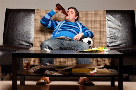 fat man balls - soccer fan is sitting on sofa with beer at home Stock Photo - Budget Royalty-Free & Subscription, Code: 400-04358888