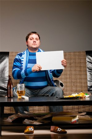 fat man balls - soccer fan is sitting on sofa with beer at home Stock Photo - Budget Royalty-Free & Subscription, Code: 400-04358889