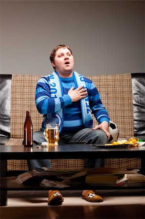 fat man balls - soccer fan is sitting on sofa and listening for a hymn with beer at home Stock Photo - Budget Royalty-Free & Subscription, Code: 400-04358895