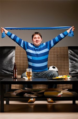 fat man balls - soccer fan is sitting on sofa with beer at home and holding scarf. Stock Photo - Budget Royalty-Free & Subscription, Code: 400-04358896