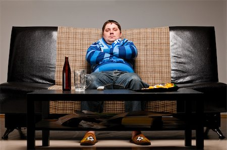 fat man balls - soccer fan is sitting on sofa with beer at home Stock Photo - Budget Royalty-Free & Subscription, Code: 400-04358891