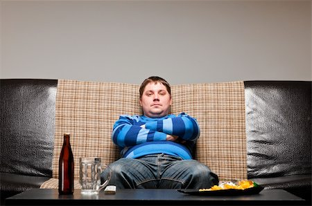 fat man balls - soccer fan is sitting on sofa with beer at home Stock Photo - Budget Royalty-Free & Subscription, Code: 400-04358892
