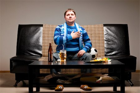 fat man balls - soccer fan is sitting on sofa and listening for a hymn with beer at home Stock Photo - Budget Royalty-Free & Subscription, Code: 400-04358893