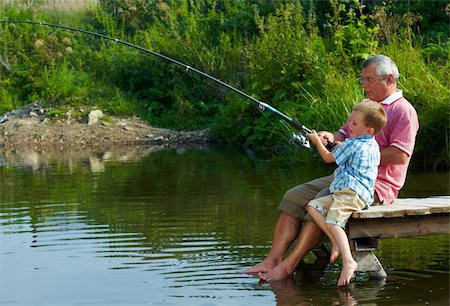 pressmaster (artist) - Photo of grandfather and grandson sitting on pontoon with their feet in water and fishing on weekend Stock Photo - Budget Royalty-Free & Subscription, Code: 400-04364673