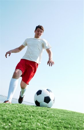 Portrait of a soccer player going to kick ball on football field Stock Photo - Budget Royalty-Free & Subscription, Code: 400-04361735