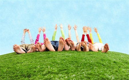 Image of several children lying on the grass and stretching their hands to the sun Stock Photo - Budget Royalty-Free & Subscription, Code: 400-04376511