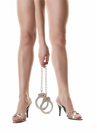A pair of long female legs and hand holding handcuffs. Isolated on white background Stock Photo - Budget Royalty-Free & Subscription, Code: 400-04371515