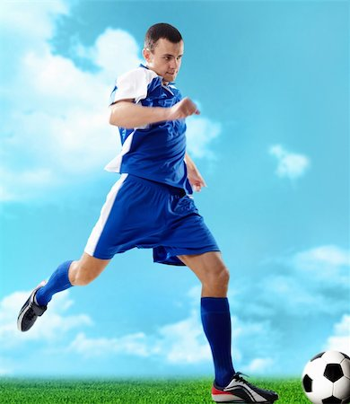 Portrait of a soccer player with ball on a blue background Stock Photo - Budget Royalty-Free & Subscription, Code: 400-04373299