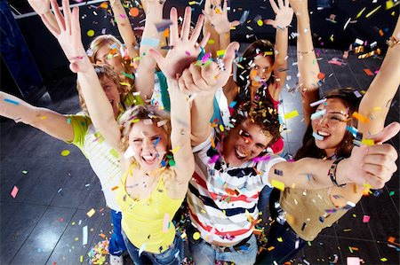Photo of excited teenagers in confetti raising their arms expressing joy Stock Photo - Budget Royalty-Free & Subscription, Code: 400-04373322