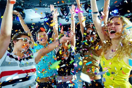 Photo of excited teenagers in confetti raising their arms expressing joy Stock Photo - Budget Royalty-Free & Subscription, Code: 400-04373774