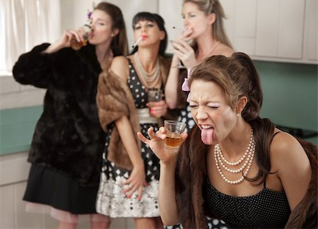 Woman reacts to strong alcohol while friends smoke and drink in the kitchen Stock Photo - Budget Royalty-Free & Subscription, Code: 400-04380616