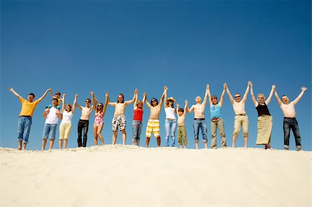 pressmaster (artist) - Image of many friends standing on sandy beach with their arms raised against blue sky Stock Photo - Budget Royalty-Free & Subscription, Code: 400-04381013