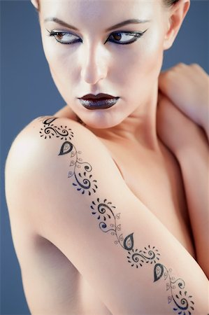 Portrait of topless woman with tattoo on arm looking aside Stock Photo - Budget Royalty-Free & Subscription, Code: 400-04395251
