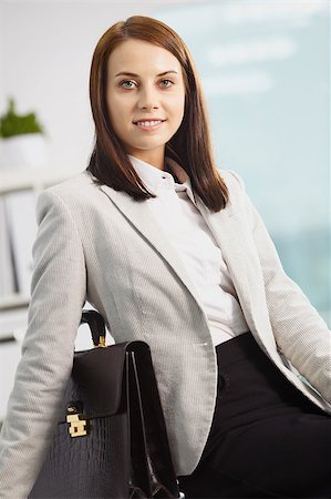 pressmaster - Portrait of smiling businesswoman with briefcase looking at camera Stock Photo - Budget Royalty-Free & Subscription, Code: 400-04397017