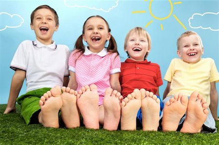 Group of happy children lying on a green grass Stock Photo - Budget Royalty-Free & Subscription, Code: 400-04391857