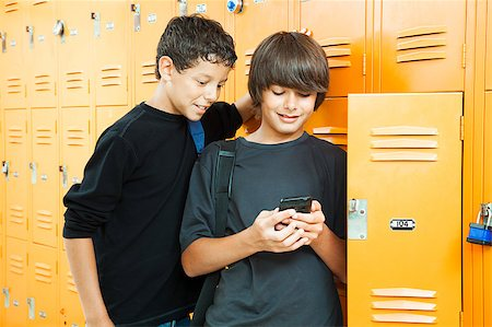photo of class with misbehaving kids - Two teenage boys playing a hand held video game in school by their lockers. Stock Photo - Budget Royalty-Free & Subscription, Code: 400-04406957