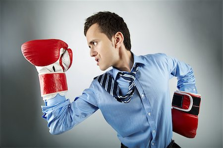Portrait of businessman in boxing gloves posing in front of camera Stock Photo - Budget Royalty-Free & Subscription, Code: 400-04407486