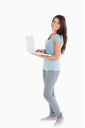 Attractive woman relaxing with her laptop while standing against a white background Stock Photo - Budget Royalty-Free & Subscription, Code: 400-04416015