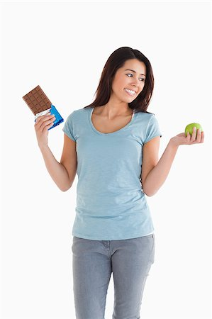 Good looking female holding a chocolate bar and an apple while standing against a white background Stock Photo - Budget Royalty-Free & Subscription, Code: 400-04416079