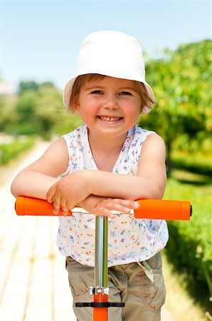 raysay (artist) - Little adorable girl posing with orange scooter in the park Stock Photo - Budget Royalty-Free & Subscription, Code: 400-04416785
