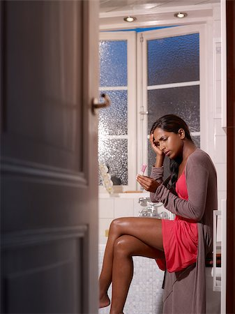 black woman with pregnancy test in bathroom, getting bad news. Vertical shape Stock Photo - Budget Royalty-Free & Subscription, Code: 400-04421840