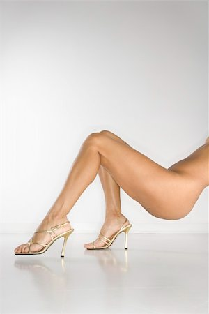 Lower half of nude woman wearing high heel shoes against white background. Stock Photo - Budget Royalty-Free & Subscription, Code: 400-04450916